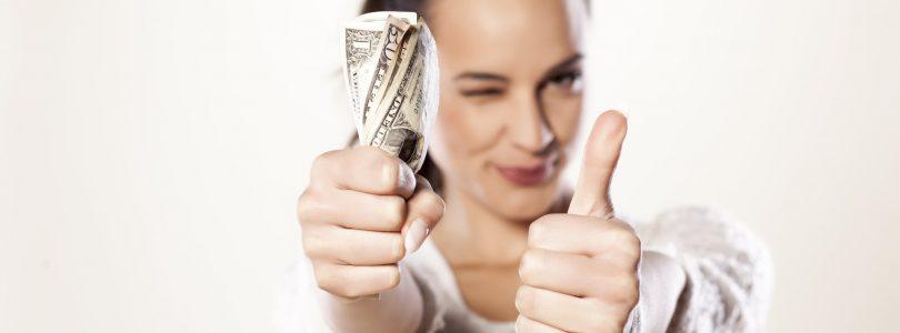 Senario Pinjaman Peribadi - Wanita memegang wang tunai sambil tunjuk thumbs up